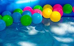 在一个小水池的色的球游泳 免版税图库摄影