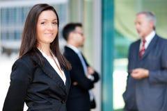 在一个小组的年轻女实业家室外的商人前面 库存照片