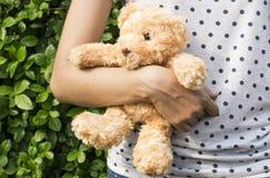 在一个少妇的胳膊的玩具熊 免版税库存图片