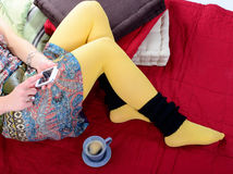 在一个少妇的腿的手机 免版税库存照片