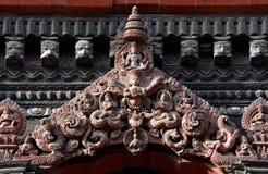 在一个尼泊尔寺庙门的被雕刻的木细节 免版税库存照片