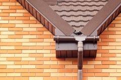 在一个屋顶的新的白色雨天沟有排水系统、石上漆的金属瓦片、塑料房屋板壁下端背面和房檐的 免版税库存图片