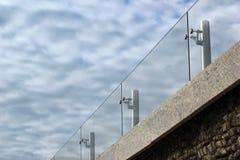 在一个屋顶的玻璃扶手栏杆反对多云天空背景 免版税图库摄影