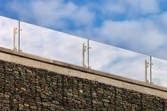 在一个屋顶的玻璃扶手栏杆反对多云天空背景 库存图片