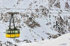 在一个山沟的黄色缆车在冬天 免版税库存照片