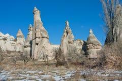 在一个山谷的圆锥形的岩石与干草和树 免版税库存图片