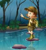 在一个岩石上的一个女孩在河 免版税库存图片