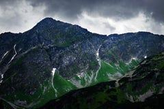 在一个岩石峰顶的黑暗的天空在山 免版税库存图片
