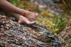 在一个岩石的女性脚在夏天 免版税库存图片