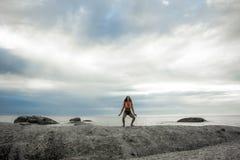 在一个岩石的妇女着陆在Bakovern海滩,开普敦的日落 免版税库存照片