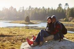 在一个岩石的混合的族种夫妇在看对照相机的乡下 免版税图库摄影