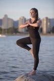 在一个岩石的瑜伽在海边 免版税库存图片