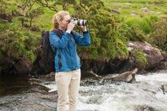 在一个岩石的白肤金发的身分在拍照片的小河 免版税库存照片