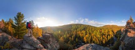 在一个岩石秋天顶部的背包徒步旅行者在黎明 圆柱形全景360度 免版税库存图片