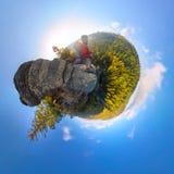 在一个岩石秋天顶部的背包徒步旅行者在黎明 球状程度全景360 180一点行星 免版税库存图片