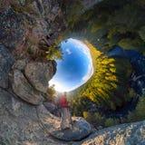 在一个岩石秋天顶部的背包徒步旅行者在黎明 球状程度全景360 180一点行星 库存照片