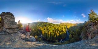 在一个岩石秋天顶部的背包徒步旅行者在黎明 等距离球状的全景360 180度 库存图片