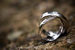 在一个岩石背景的婚戒 免版税库存照片