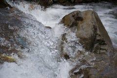 在一个岩石附近的水搅动在河 免版税库存照片