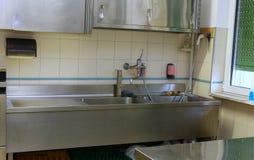 在一个工业厨房下沉和工作凳在学校加州 免版税库存图片