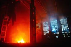 在一个工业工厂或仓库里面,工业事故保险的一个大车间的夜火 免版税图库摄影