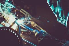 在一个工业车间供以人员在一个工作表上的焊接的钢管,生产蓝色和绿色烟,热的火花 库存图片