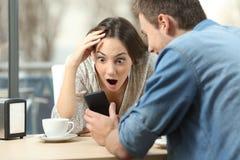 在一个巧妙的电话的惊奇的妇女观看的媒介 免版税库存图片
