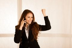 在一个巧妙的电话的有吸引力的女商人谈话在她的办公室ge中 免版税库存图片