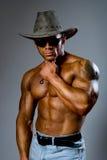 在一个帽子和太阳镜的肌肉男性在灰色背景 免版税库存照片
