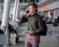 在一个帽子身分的商人在机场,谈话由手机 库存图片