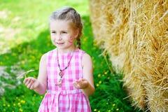 在一个干草堆附近的可爱的小女孩在晴朗的夏日 免版税库存图片