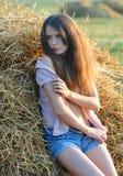 在一个干草堆附近的女孩被解扣的衬衣的 免版税库存照片