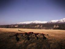 在一个干草领域的摊晒机与葡萄酒作用 库存图片