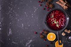 在一个平底锅的新鲜的自创酸果蔓酱在与驱散的黑暗的木背景成熟莓果 免版税库存图片