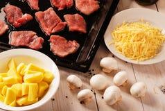 在一个平底锅的未加工的使有大理石花纹的牛排用土豆、乳酪和蘑菇 库存照片