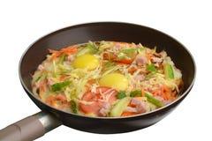 在一个平底锅的煎蛋卷有在白色背景的菜的 免版税库存图片