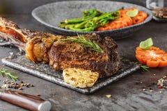 在一个平板炉的切的罕见的烤或烤印第安战斧牛排用新鲜的迷迭香和蕃茄在关闭看法 库存图片