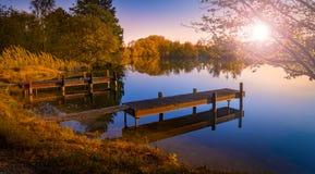 在一个平静的湖的木跳船日落的 免版税库存图片