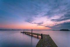 在一个平静的湖的紫色黄昏 库存照片