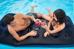 年轻在一个床垫的夫妇饮用的鸡尾酒在享受和一个暑假,顶视图的游泳池 库存图片