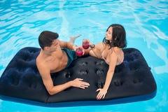 在一个床垫的愉快的男人和妇女饮用的鸡尾酒在享受和一个假日,顶视图的水池 库存图片