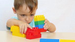 在一个建设者的色的块的外面男孩修造在白色背景的一张桌上 股票录像