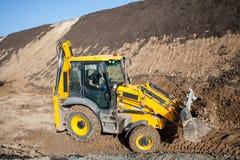 在一个建造场所的拖拉机装载者反向铲挖掘机的装载者有蓝天和剧烈的云彩的 免版税库存照片