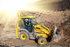 在一个建造场所的拖拉机装载者反向铲挖掘机的装载者有蓝天和剧烈的云彩的 库存照片