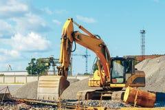 在一个建造场所的被跟踪的挖掘机在堆瓦砾中 免版税库存照片