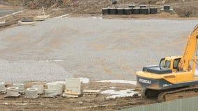 在一个建造场所的黄色挖掘机在夏天 股票录像