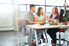 在一个开放概念办公室一起群策群力在一种数字式片剂的Unposed小组创造性的企业家 库存照片