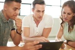 在一个开放概念办公室一起群策群力在一种数字式片剂的Unposed小组创造性的企业家 免版税库存图片