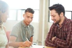 在一个开放概念办公室一起群策群力在一种数字式片剂的Unposed小组创造性的企业家 免版税库存照片