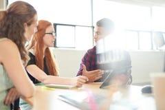 在一个开放概念办公室一起群策群力在一种数字式片剂的Unposed小组创造性的企业家 库存图片